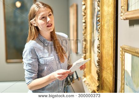 Brunette Girl Visitor Holding Guide Book Standing Near Pictures In Museum Of Arts