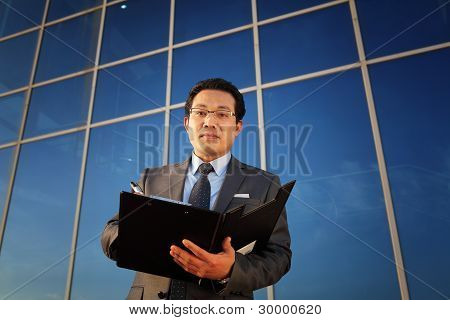 Businessman Holding A Notepad Front Office