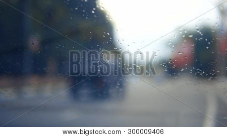 Rain On The Glass. Rain Outside The Window On The Background Of The Road. Drops Of Water Falling On