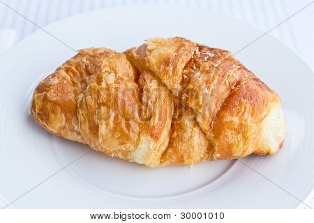 The fresh croissant isolated on white plate