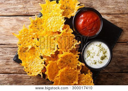 Delicious Appetizer Of Cheddar Cheese Chips With Herbs Served With Sauces Close-up. Horizontal Top V