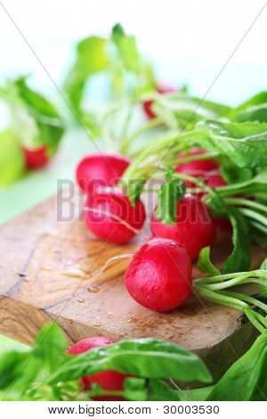 Fresh radishes with green leaves on wooden board, soft focus