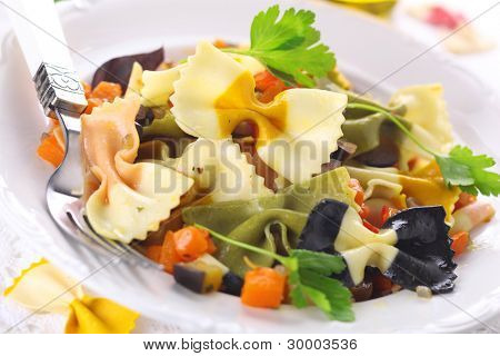 Colorful pasta farfalle with vegetables on white plate