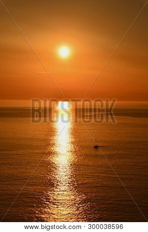 Sunset; Sailboat Returning To Port In Baiona