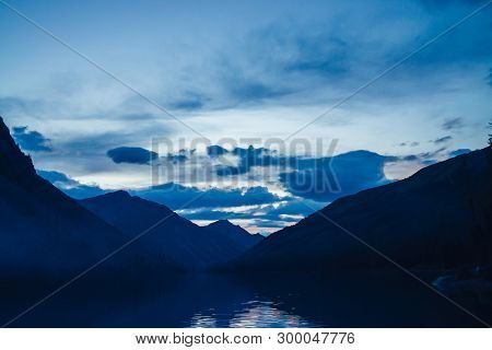 Amazing Blue Silhouettes Of Mountains On Dusk. Dawn Sky Reflected In Mountain Lake. Wonderful Atmosp