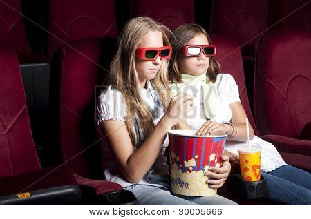 two beautiful girls watching a movie at the cinema