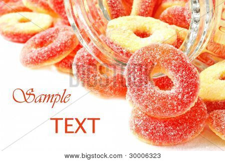 Peach flavored candy rings spilling from glass jar on white background with copy space.  Macro with shallow dof.