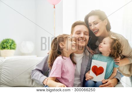 Happy father's day! Children daughters and their mom are congratulating dad and giving him postcard. Daddy and girls smiling and hugging. Family holiday and togetherness.