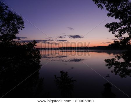 Sunrise mirrored in glassy lake