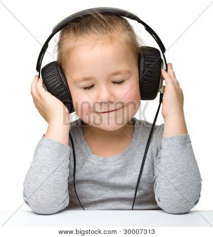 Cute little girl enjoying music using headphones, isolated over white