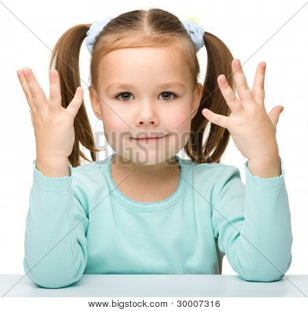 Portrait of a cute little girl sitting at table and showing how old she is using fingers, isolated over white