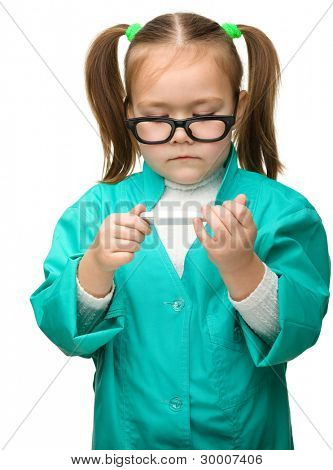 Cute little girl is playing doctor studying a thermometer, isolated over white
