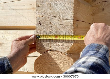 Carpenter Measures Wooden Logs