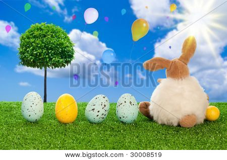Easter bunny with easter eggs overlooking sky filled with balloons