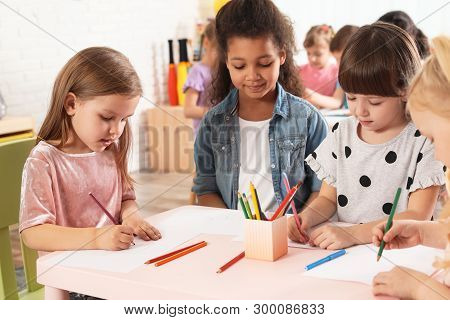 Adorable Children Drawing Together At Table Indoors. Kindergarten Playtime Activities