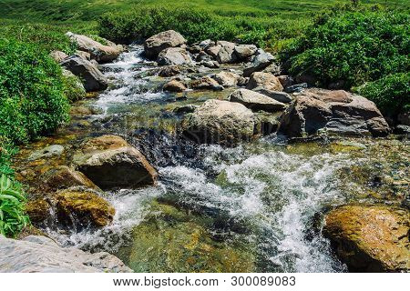 Mountain Creek With Big Boulders Near Green Meadow In Sunny Day. Clean Water Stream In Fast Brook In