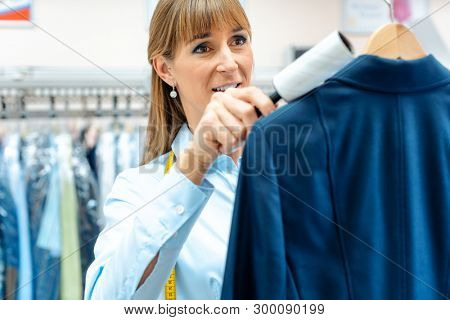 Dedicated woman in dry cleaning store is using lint roller to clean a jacket