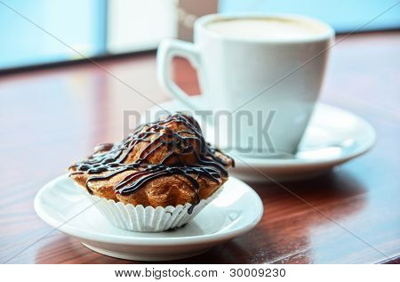 Chocolate muffins with and coffee cup on orange table