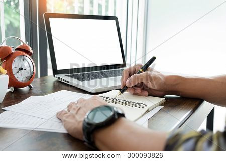Young Caucasian Man Working At Home Planning Work Writing Note On Some Project With His Laptop On A