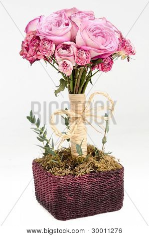 Bouquet of pink roses in a handmade basket, isolated