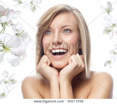 portrait of attractive  caucasian smiling woman blond isolated on white studio shot with spring flowers