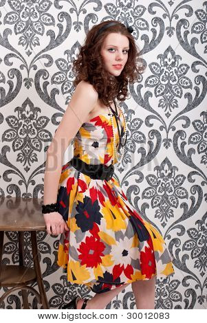Young beautiful woman in retro dress on vintage wallpaper background
