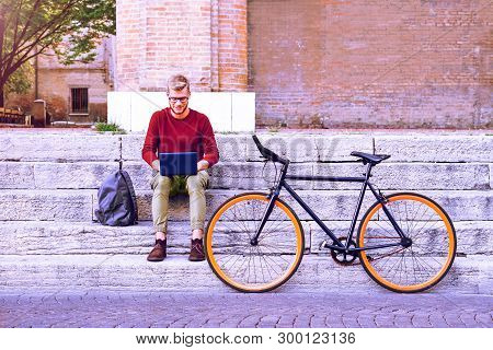 Commuter Man With Laptop And Sport Bike Sitting On Old City Steps - University Student Using Noteboo