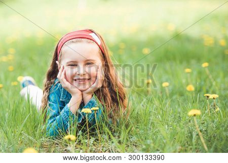 Adorable funny little girl laying on floral green field on sunny day