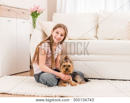 Cute puppy and happy young girl playing in the living room