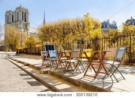 Autumn In Paris, Tables And Chairs Of An Outddoor Cafe Next To Notre Dame Cathedral. This Image Is T