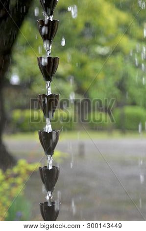 Rain Is Flowing Down A Japanese Rain Chain. Each Cup Is Designed Like A Flower. Heavy Drops Of Rain