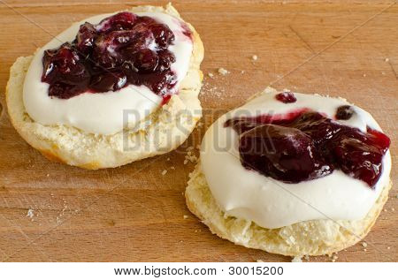 Biscuits (scones) with whipped cream and blackcurrant jam