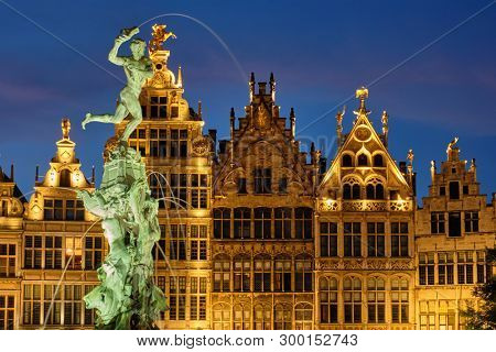 Antwerp famous Brabo statue and fountain on Grote Markt square illuminated at night and old houses. Antwerp, Belgium