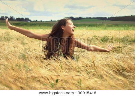 beautiful young woman relaxing in golden field
