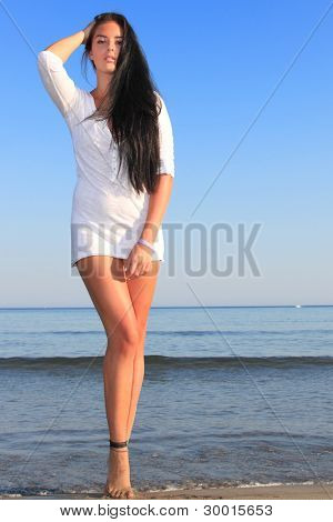 Attractive woman with beautiful long dark hair posing on the beach in Greece