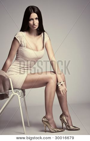 elegant young woman in short dress, high heels, sit on chair, studio shot, small amount of grain added