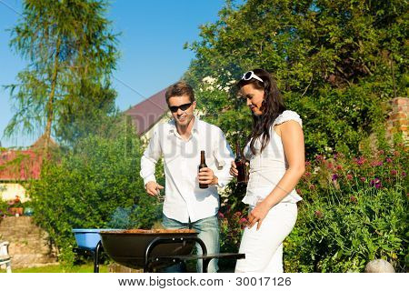 Couple - man and woman - doing the barbeque together in their garden in summer