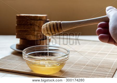 Jar of Honey with Honey Dipper with Toast Bread In the Background on a Wooden Table Setup poster