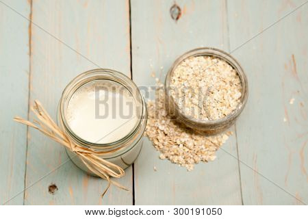 Oat Milk A Glass Of Oat Milk With Oat Grains On A Wooden Table - Vegan Milk