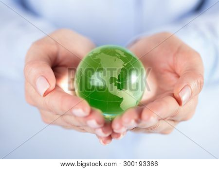 Glass green globe in hands