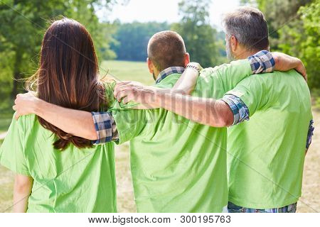 Three environmentalists or activists in green shirt hugging each other