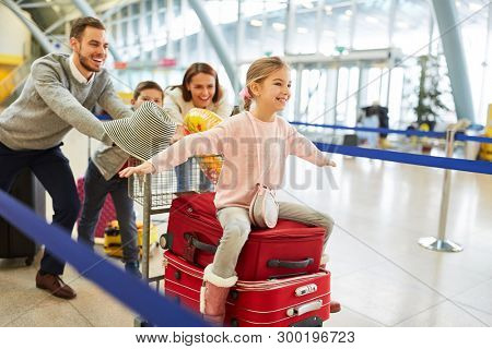 Happy family and children on the way to family vacation in airport terminal