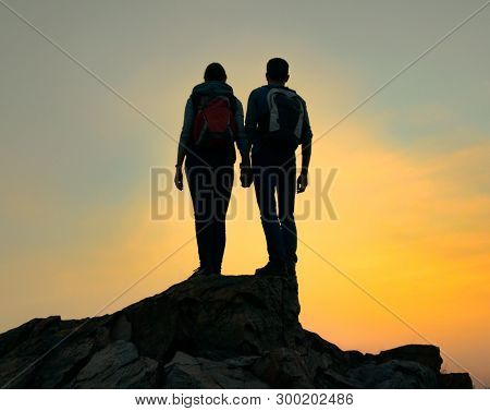 Couple of Young Travelers with Backpack Standing on the Top of the Rock at Warm Summer Sunset. Travel and Adventure Concept.