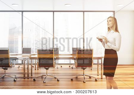 Thoughtful Blonde Businesswoman Standing In Panoramic Office Meeting Room With Wooden Floor And Long