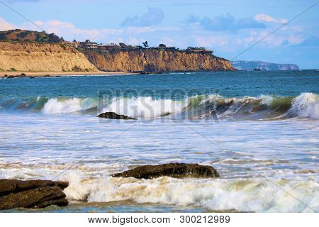 Waves Crashing On Shore To A Rugged Coastline With Rocky And Sandy Beaches Besides Sandstone Bluffs