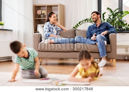family, leisure and people concept - happy mother and father sitting on sofa and looking at their children drawing at home