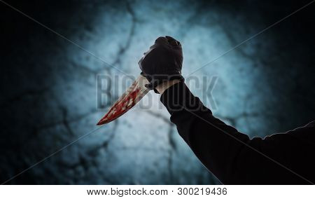 crime scene, murder and killing concept - close up of criminal or murderer hand in leather glove with blood on knife over dark cracked stone background (staged photo)