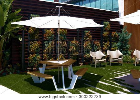 Outdoor Patio Furniture Including Contemporary Style Tables And Chairs With Umbrellas Besides A Vert
