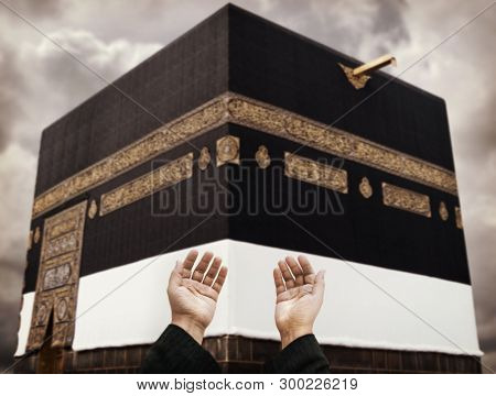 Muslim hands praying to God in front of Kaaba