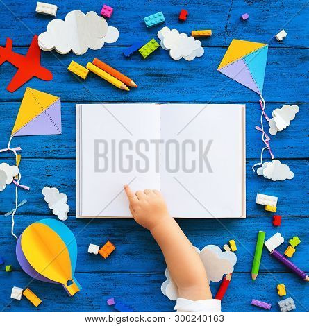 Сolourful Toy Bricks, Paper Crafts And Blank Book With Child Hands On Blue Wood Board. School Or Pre